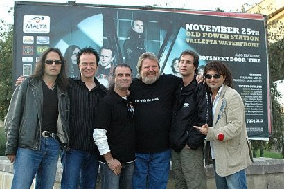 Peter & Band In Front Of Malta Billboard